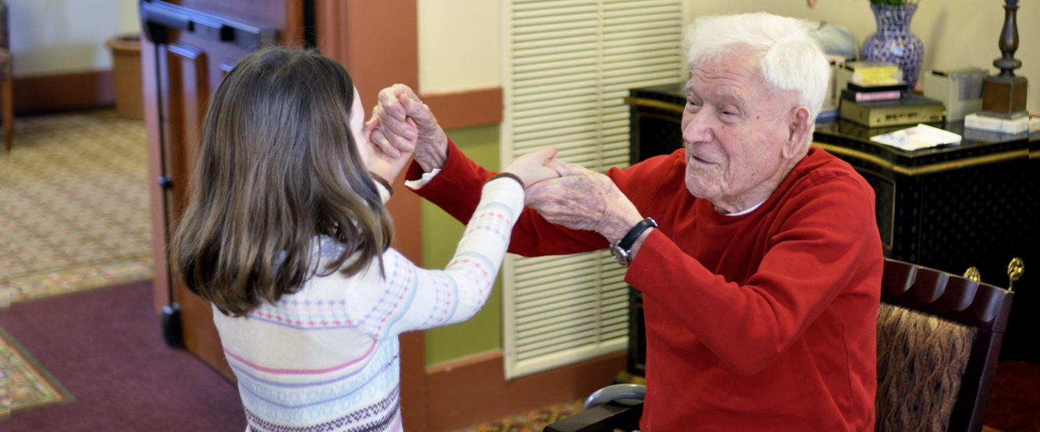 photo of a senior man chair dancing with a young girl