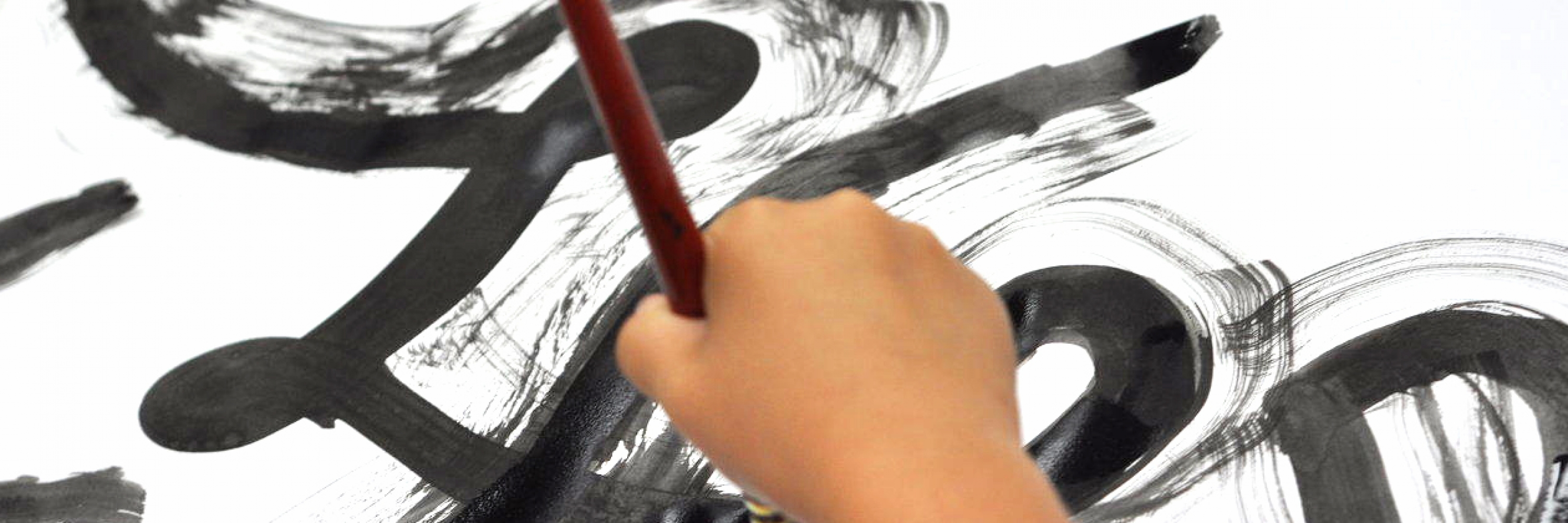 photo of a child's hand painting a black brush stroke