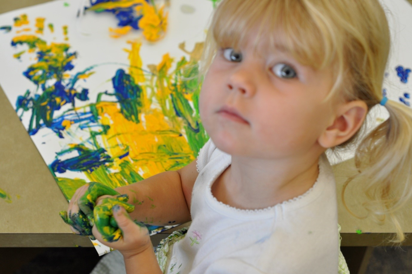 photo of young girl with paint colored hands next to her finger painted art piece