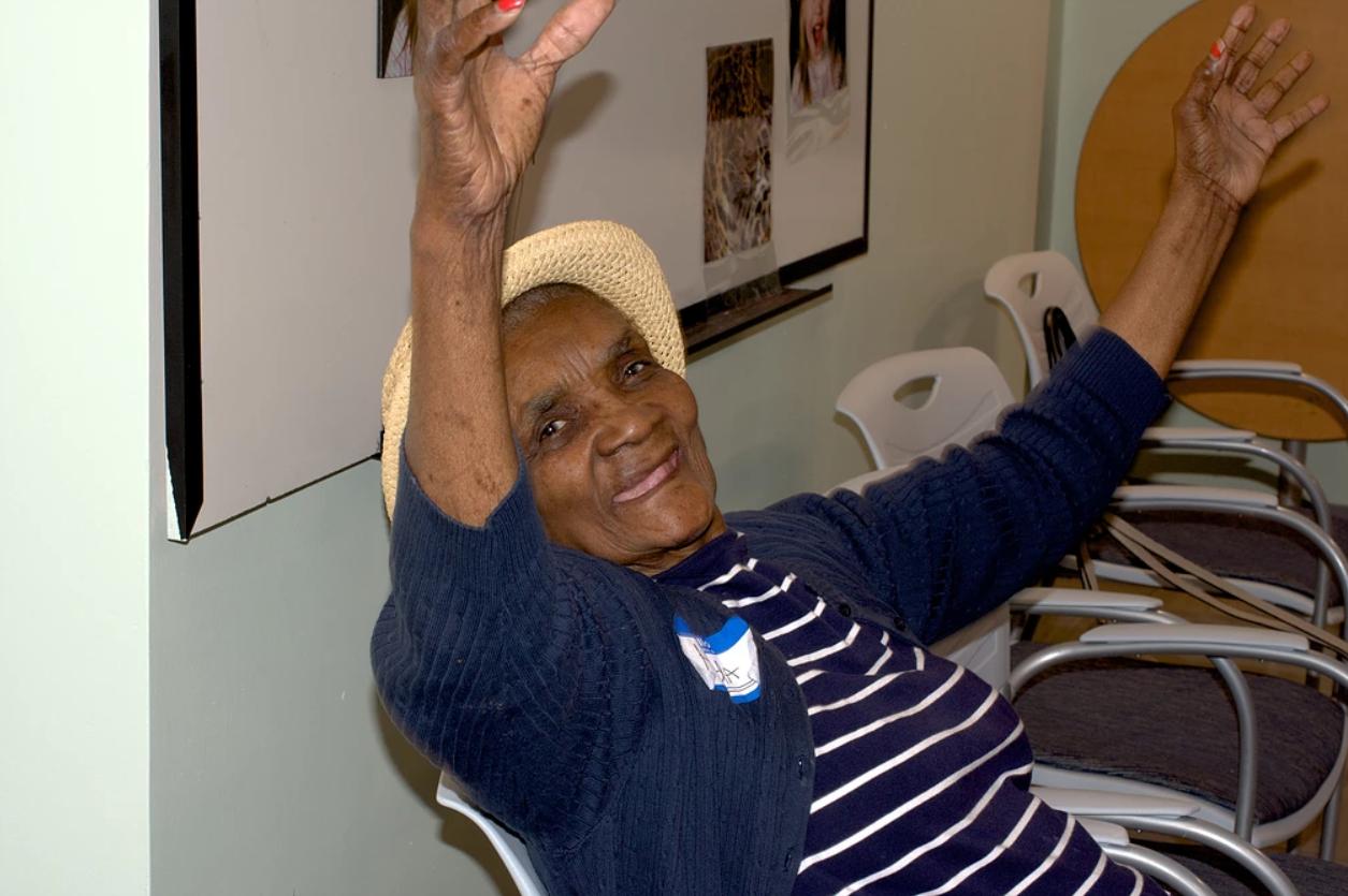 photo of smiling woman enjoying music at senior center