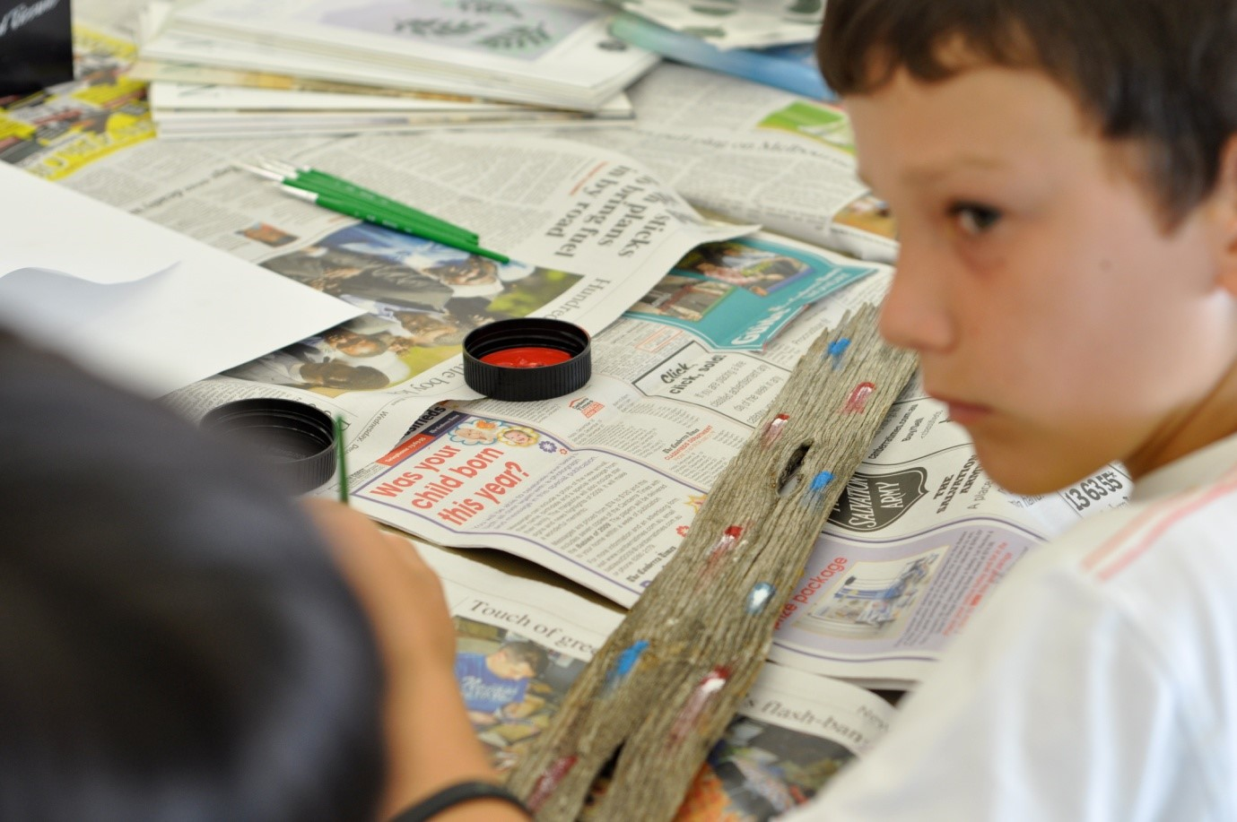 photo of young boy painting on a piece of drift wood