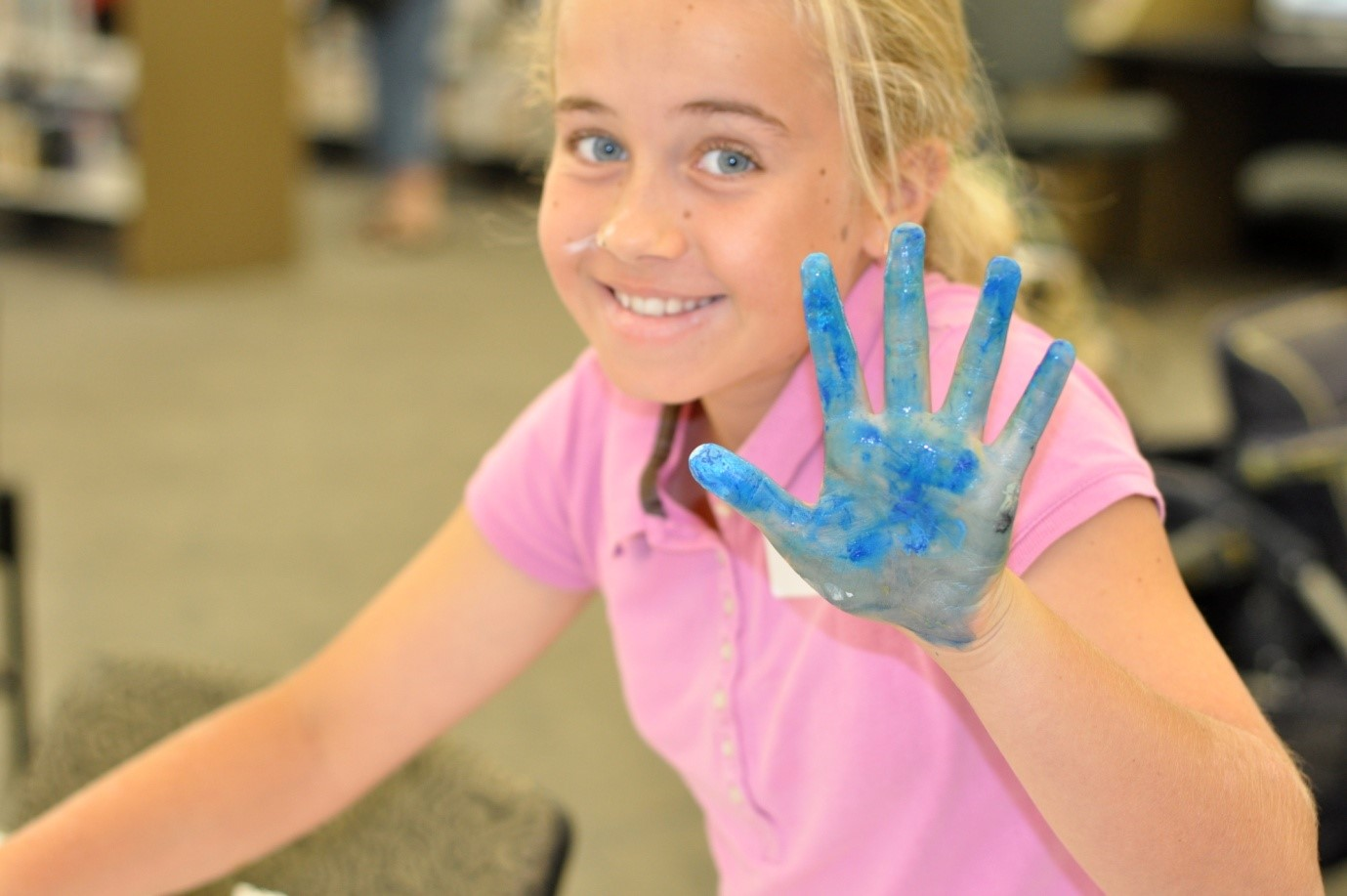 photo of smiling girl holding up a hand covered in blue paint