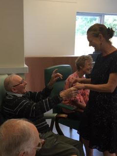 photo of instructor at senior center laughing with senior man
